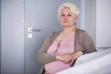 Portrait of confident senior woman sitting in house
