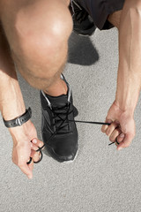 Low section of sporty man tying shoelace on street