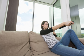 Young woman watching TV on sofa at home