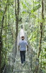 Man walking across hanging bridge in rainforest,, La Fortuna, Arenal, Costa Rica, Central America