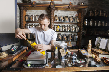 Male owner scooping ingredient into paper bag at tea store