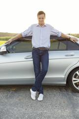 Full length portrait of smiling young man leaning on car at countryside
