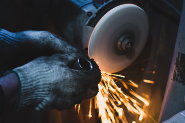 Factory worker at workshop grinding steel rod with abrasive disc and flying sparks