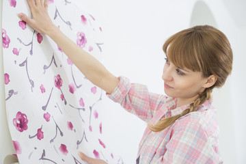 Woman applying wallpaper on wall in new house