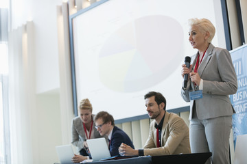 Businesswoman giving presentation in seminar hall