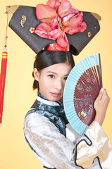 Beautiful Chinese Woman wearing traditional outfit against yellow background
