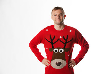 Caucasian man with hand on hips whilst wearing a christmas jumper