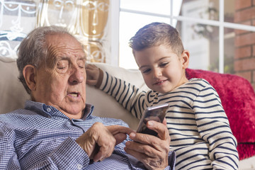 Grandfather and grandson looking a smart phone at home