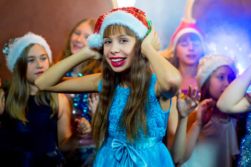 Group of cheerful young girls celebrating Christmas. Headphones