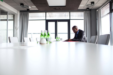 Side view of young businessman sitting at conference table