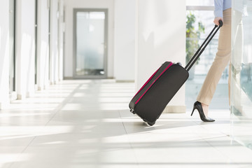 Low section of businesswoman with luggage leaving airport