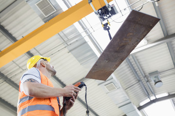 Low angle view of manual worker operating crane lifting sheet metal in industry