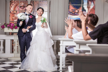 Wedding guests applauding for newlywed couple holding flowers in church