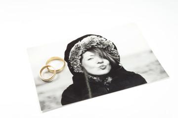 Zwei Eheringe und ein Foto einer Frau