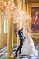 Cheerful wedding couple dancing in church