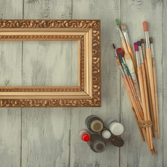 Brushes, paints and a picture frame