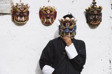 Man displaying traditional masks, Thimphu, Bhutan, Asia