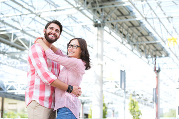 Happy couple looking away while embracing outside building