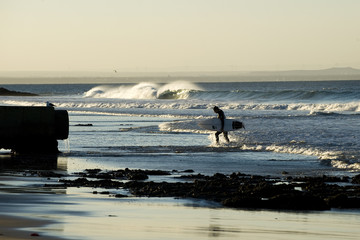 Surfer leaving the water after an evening session
