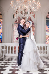 Side view portrait of smiling wedding couple standing in church