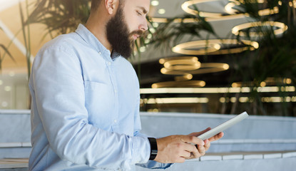 Side view. Young bearded businessman wearing blue shirt using tablet computer. Man checks email, browsing internet, chatting on digital tablet. Lights in shape of circles in soft focus in background.