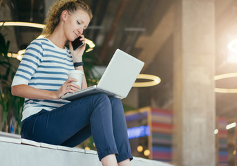 Young woman sitting in room with modern interior and uses laptop while talking on cellphone and holding cup of coffee.Girl browsing internet,chatting,blogging, checking email.Online shopping,learning.