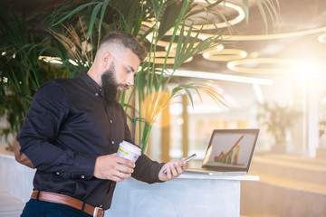 Young bearded businessman in brown shirt standing and is using smartphone while holding cup of coffee.Nearby is laptop.Diagram on computer screen.Man uses digital gadget.Guy chatting,blogging.