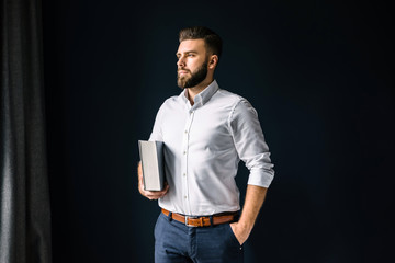 Young bearded businessman, dressed in a white shirt standing near the window on the background of a dark wall and looking out the window. In his hand man holding a thick book.