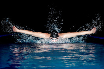 Man in black cap in swimming pool. Butterfly style