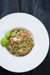 White plate with spinach risotto, overhead view, studio shot
