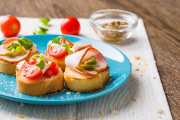 Bruschetta with tomato, cheese and bacon