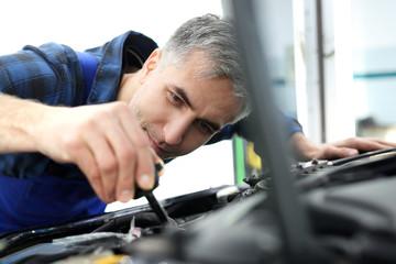 Mechanik dokręca zawór zbiornika płynu kierowniczego. Mechanik samochodowy wymienia płyn układu kierowniczego.