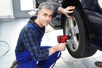 Fototapeta Warsztat samochodowy, serwis opon. Mechanik samochodowy dokręca kluczem pneumatycznym koła w samochodzie. obraz