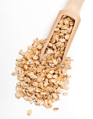 Uncooked oat flakes in wooden scoop on white background. Top view, close up, high resolution product