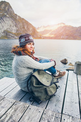 Woman traveler with a backpack sitting on a wooden pier.