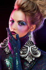 Young attractive blonde girl in bright art-makeup, in purple tones. Rhinestones and glitter body painting.