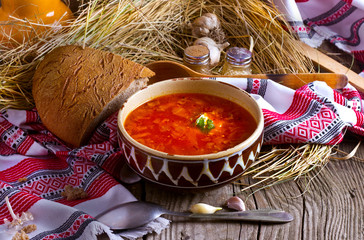 clay plate with borscht soup on a wooden table with hay and a towel, Ukrainian national dish