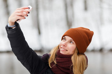 Blonde makes selfie in park