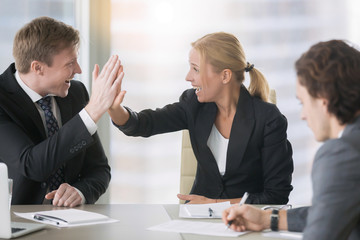 Businessman and businesswoman giving a high five