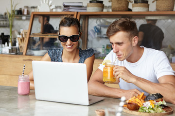 People, technology and leisure concept. Cute couple having fun, sitting at cafe in front of laptop computer: man sipping orange juice and woman in sunglasses absorbed in watching something on notebook