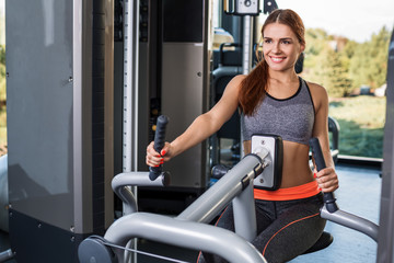 Muscular young woman doing exercises on the simulator in the gym