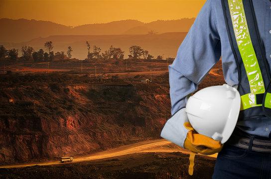 Engineer holding white helmet with coal mining