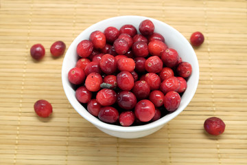 Cranberries in a round white bowl and scattered blueberries on brown straw mat top view