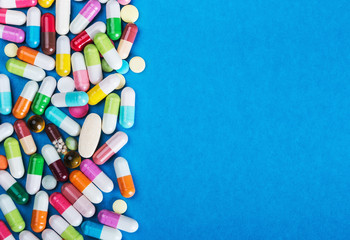 many scattered Colorful pills on blue background