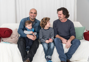 Couple of mature homosexual men sitting on sofa with their two children