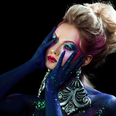 Young attractive blonde girl in bright art-makeup, clasped hands a head. Rhinestones and glitter body painting.