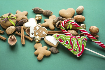 Christmas composition with bells, cookies, spices, pine cones, nuts on natural craft background
