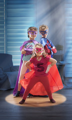 Three childs dressed as superhero are standing in a living room