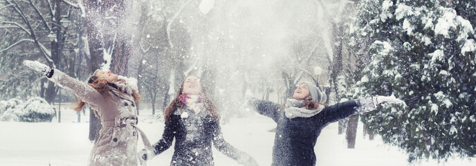 Happy teenage girls throwing snow in the air on beautiful winter day