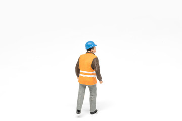 Miniature people worker safety construction concept on white bac
